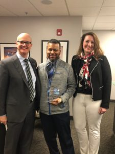 ChanceLight CEO, Mark Claypool, and ChanceLight COO, Alison O'Neill, stand smiling; with Servant Heart Award Recipient from the Corporate Division, Shaun Woodyard, smiling and holding his award standing in between them.